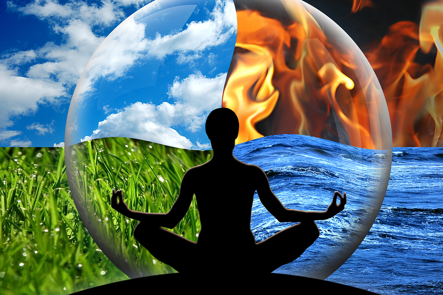 Female yoga figure in a transparent sphere composed of four natural elements (water fire earth air) as a concept for controlling emotions and power over nature.